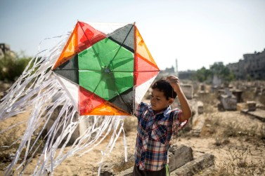 A chil plays with his kite in the cemetery of Jabaliya refugee camp, Gaza Strip, June 8, 2017. Jabaliya refugee camp has a registered population of more than 100,000 inhabitants, making it the most overcrowded refugee camp in the Gaza Strip.